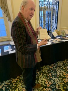 Alexander McCall Smith poses with one of his favorite display items, George H. Young's textbook Elementary Course of the Principles of Detection... (1914). Photo by David Taylor, 2019.