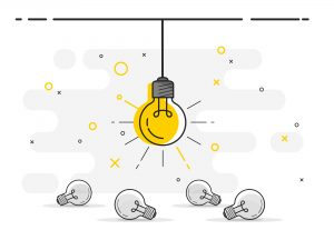 A light bulb lit up and screwed in surrounded by unlit light bulbs on the floor.