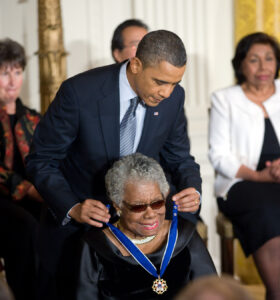 Maya Angelou, seated and beaming while she receives the presidential medal of freedom from President Obama