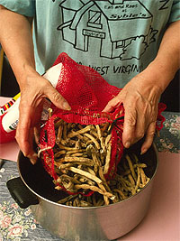 Hands emptying a bag of dried string beans into a pot.