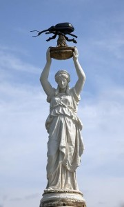 Boll Weevil Monument: the figure of a woman in robes holding a large beetle over her head.