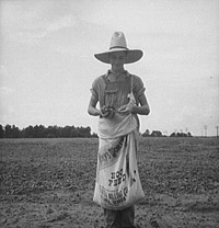 Farm boy carrying a large sack.