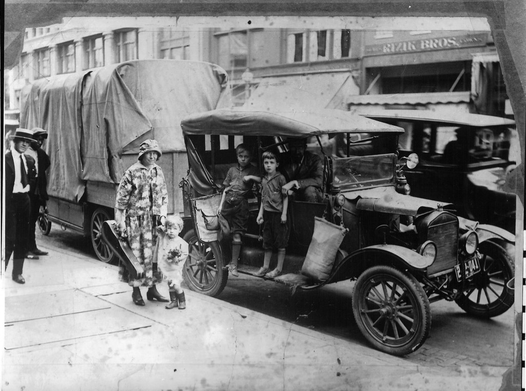 A woman with a violin case in one hand holds a toddler's hand in the other. She stands next to a car. Two young boys stand on the running board and a bearded man sits in the seat. Two onlookers peek into the frame.