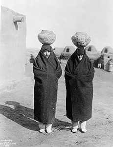 Zuni women carrying large ceramic pots on their heads