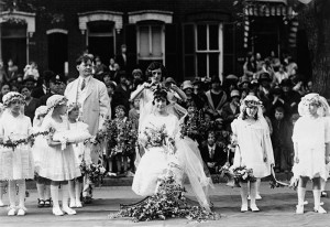 Adults and children wearing white surround a woman being crowned with flowers.