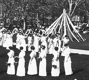 Women in white gowns carrying flowered wreaths near a May pole.