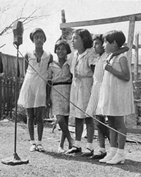 Four girls singing in front of a large miccrophone.