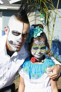 A father and daughter pose for a photograph. His makeup is half skull and half human. The girl wears the traditional costume and makeup of Santa Muerte (saint of death), combining flowers and bright colors with skull-like features.