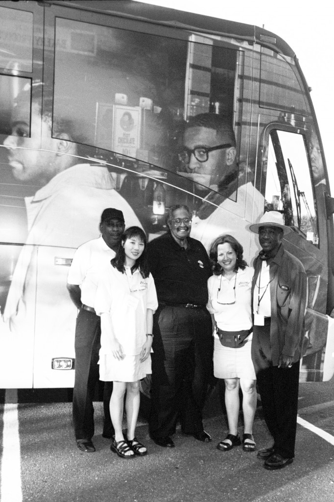 From left to right: Vern Smith, Lydia Lum (reporter), Franklin McCain (one of the Greensboro four at lunch counter sit-in), Nery Ynclan (reporter), and Lester Sloan (photographer) in front of the AARP bus with McCain's image. Photograph by Lester Sloan, © AARP 2004.
