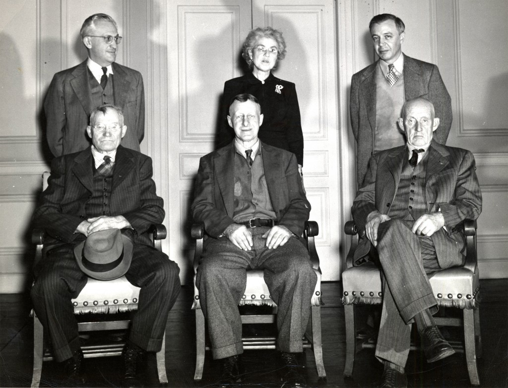 Three men sit on chairs. Behind them stand two men and a woman.