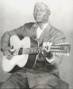 "Portrait of Huddie ""Lead Belly"" Ledbetter with guitar."