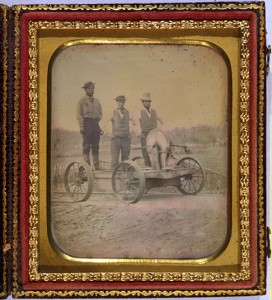 Three men standing on a railroad hand cranked car.