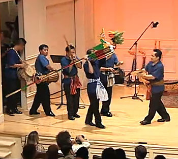 Men entering the stage carrying instruments and a large rocket.