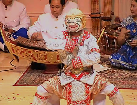 A performer in a white and red costume and monkey mask dances in front of musicians.