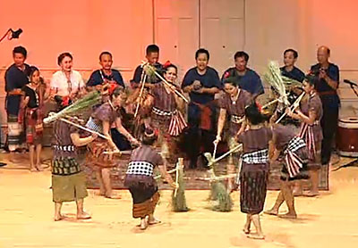 Musicians in the background stand and play drums, bells, and rattles as women dancers beat bunches of rice stalks tied to sticks against the floor in the actions of threshing rice.