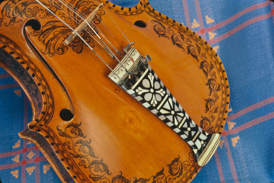 Jørgen Hyland's Hardanger fiddle, Evanston, June 6, 1977. Photo by Carl Fleischhauer. This elaborate appearance is typical of most Hardanger fiddles. Mr. Hyland learned to play Hardanger fiddle from an old Norwegian in his home town of Bergen, Norway (an area known for this style of fiddling), when he was about 10 years old.