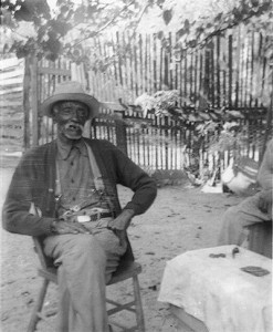 An elderly African American man seated outside.
