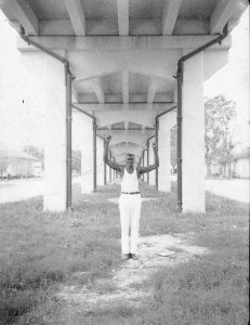 An African American man holding his hands up over his head beneath a bridge.