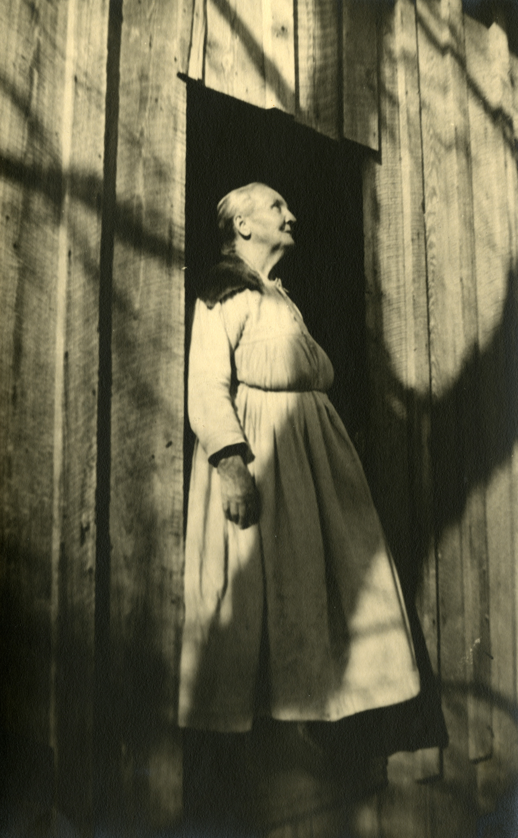 An elderly woman in a white dress standing in a doorway and looking upward.