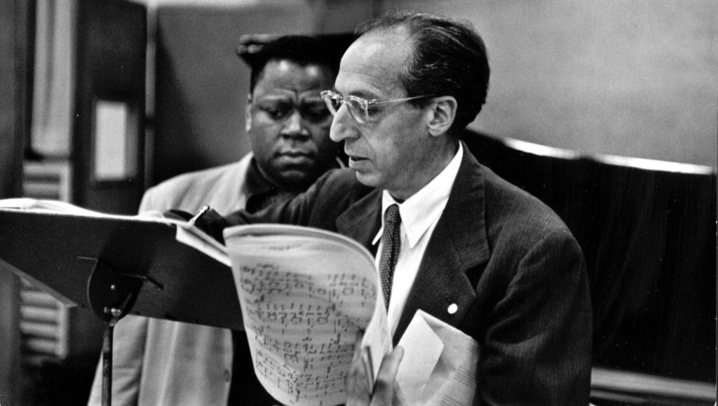 African American singer William Warfield and Jewish American composer Aaron Copland look at music on a music stand.