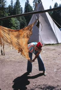 A woman scrapes an elk hide that is suspended from a pole.