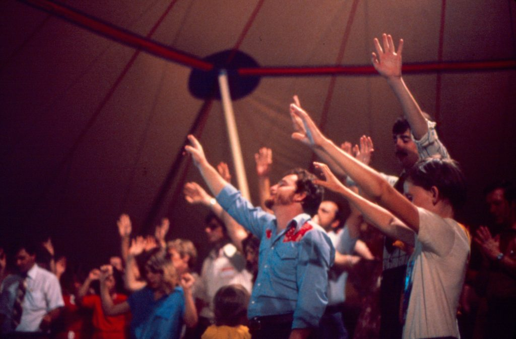 Group of people in a large tent stand with their arms raised toward the ceiling