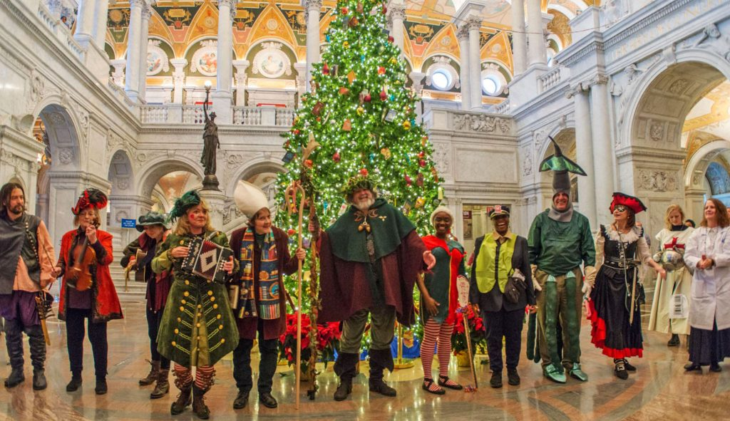 The 2016 American Folklife Center Mummers perform at the Library of Congress Holiday Party in the Great Hall of the Jefferson Building. The cast at program's end: Captain Acquisition (David Brunton), Fiddler (Cathy Kerst), Guitarist (Maya Lerman), Curly Toes (Jennifer Cutting), Bishop (Stephanie Hall), Father Christmas (Stephen Winick), Linear Feet (Valda Morris), Metro Manager (Alicia Bartlett), Arrearage Squid (George Thuronyi), Doctor Dover (Thea Austen), Processing Saint George (Sarah Lerner), and Processing Pro (Hope O'Keefe).