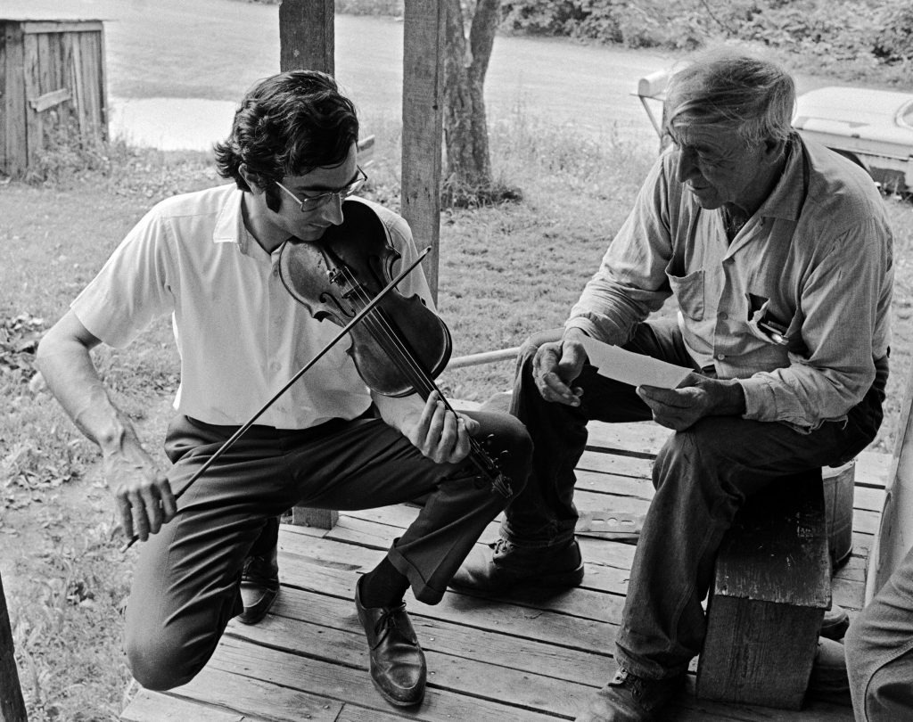 Alan Jabbour and Sherman Hammons in Stillwell, near Marlinton, West Virginia, July 1972. The pair are on the back porch of the house where Sherman's brother Burl and sisters Maggie Parker, Ruie Hammons, and Emmy Roberts lived. Photo by Carl Fleischhauer.