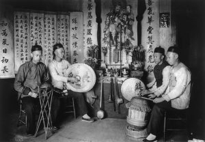 Chinese musicians holding a gong, drum, and cymbals.