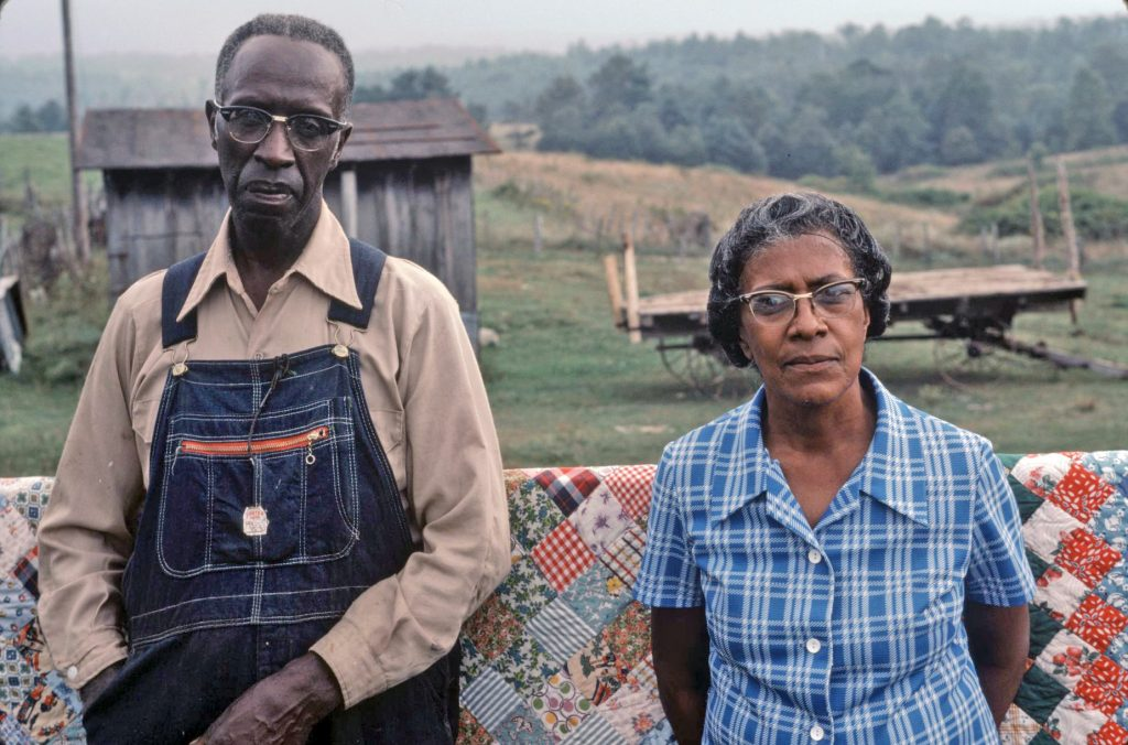 Donna Choate and her husband Sabe stand in front of a quild draped over a fence. A farm building and flatbed wagon can be seen in the background.