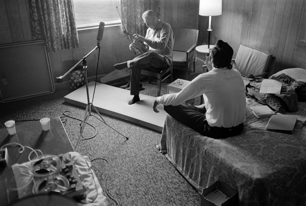 On one occasion in April 1972, boisterous household conversation, barking dogs, and passing traffic at the Hammons home made it nearly impossible to capture a clean recording of Burl's fiddle playing. Alan rented a motel room in Marlinton for the day, where he and the photographer made recordings. The photographer's foam sleeping pad is on the floor to help dampen the sound of Burl's foot-tapping.