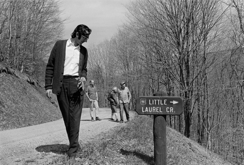 Alan Jabbour at the U.S. Forest Service sign for Little Laurel Creek, which flows into the Williams River at the bottom of the hill to the right. In the background of this April 1972 photograph are visiting friend Paul Haggard, Maggie Hammons Parker, and Burl Hammons. Maggie and Burl had accompanied their visitors to this location in order to show them one of the family's former homesites, near the mouth of Little Laurel.