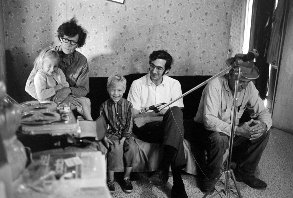 Playing back a tape recording: Allene Hammons, Sherman's wife, holding granddaughter Kay Hammons, grandson Lee Hammons, Alan Jabbour, and Sherman Hammons, at Allene and Sherman's home near the Williams River, July 1972. The photographer has forgotten the details but the position of the microphone and Lee's smile suggests that the recording included his voice.
