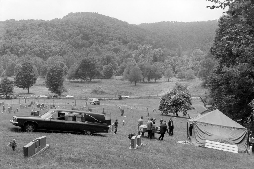 Pallbearers carry Maggie Hammons Parker's coffin to her grave in the Cochran Cemetery, not far from Edray, West Virginia, July 30, 1987. The Williams River watershed lies one mountain ridge away, to the west. In this photograph, Alan Jabbour stands just to the right of the coffin, wearing a dark suit and necktie.