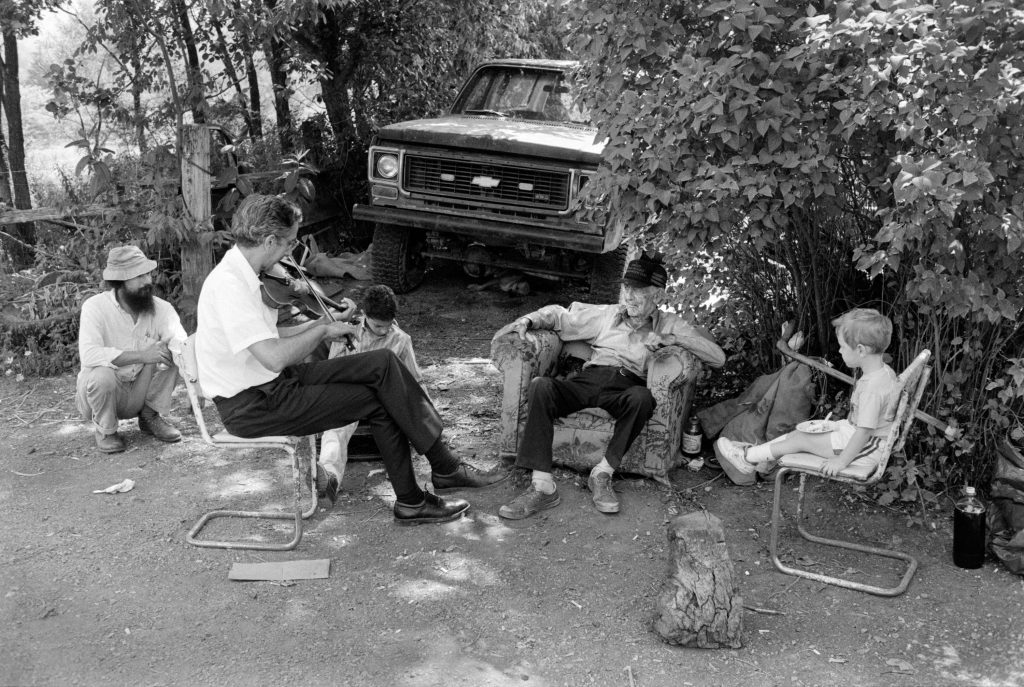 At Sherman's home after Maggie's funeral, July 30, 1987. Alan Jabbour plays fiddle for Sherman Hammons, wearing a dark hat, and two music-loving friends of the family, Mike Risch at left and Jake Bing at right. Alan's wife Karen and son Aaron also came to the funeral; in this photograph, Aaron is sitting on the ground behind his father.