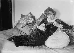 A European American women reclining on a couch playing what appears to be a small banjo.