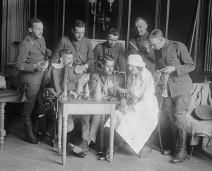 Soldiers in uniform gather around a nurse and another soldier who is learning to knit.