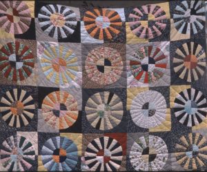 A quilt with multi-colored circles within squares as a motif.
