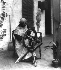 African American woman spinning flax on a spinning wheel.