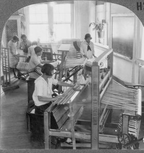 Women seated at three looms weaving.
