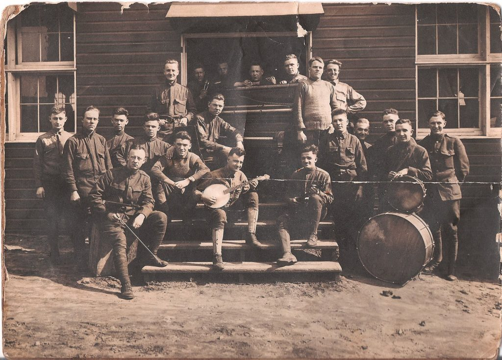 A black and white photograph of a World War I era band posing in the front entrance of a building with their musical instruments.