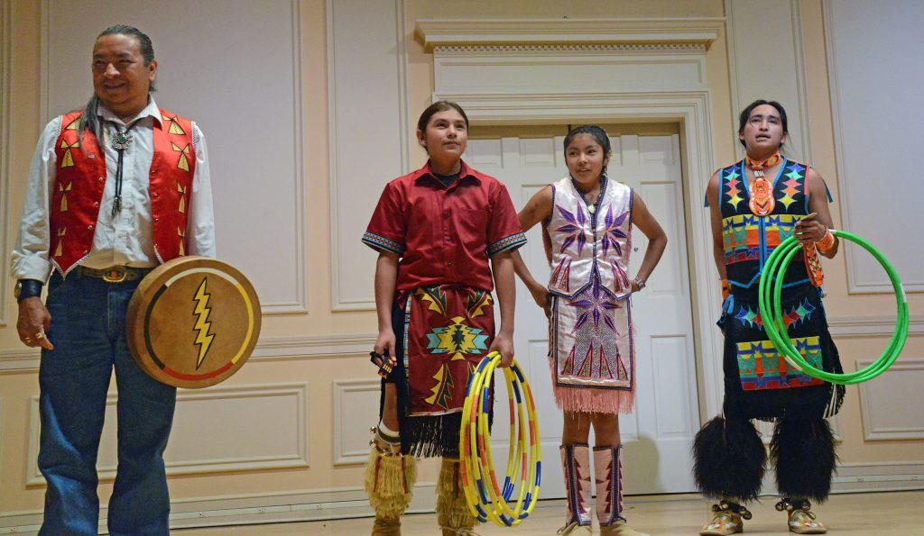 Three men and a woman on stage in Native American dress.