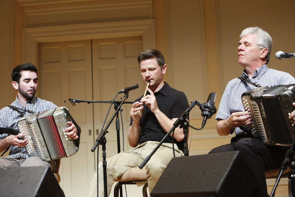 Two men play accordions and one man plays a tin whistle.