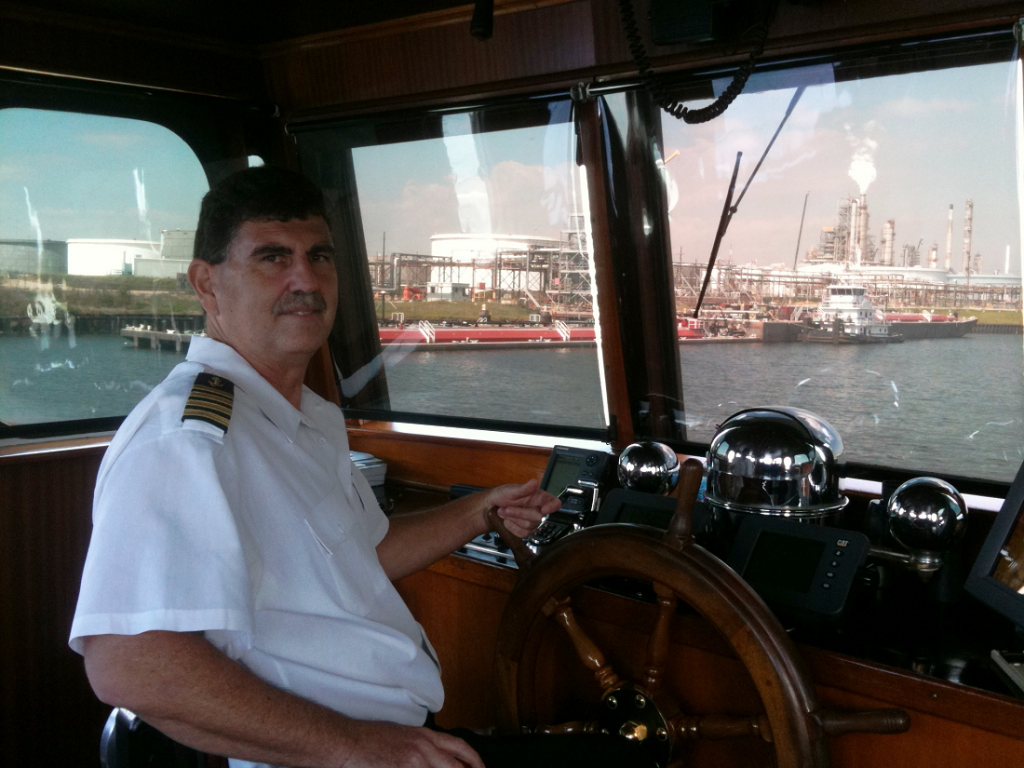 A man sits at the controls of a boat.