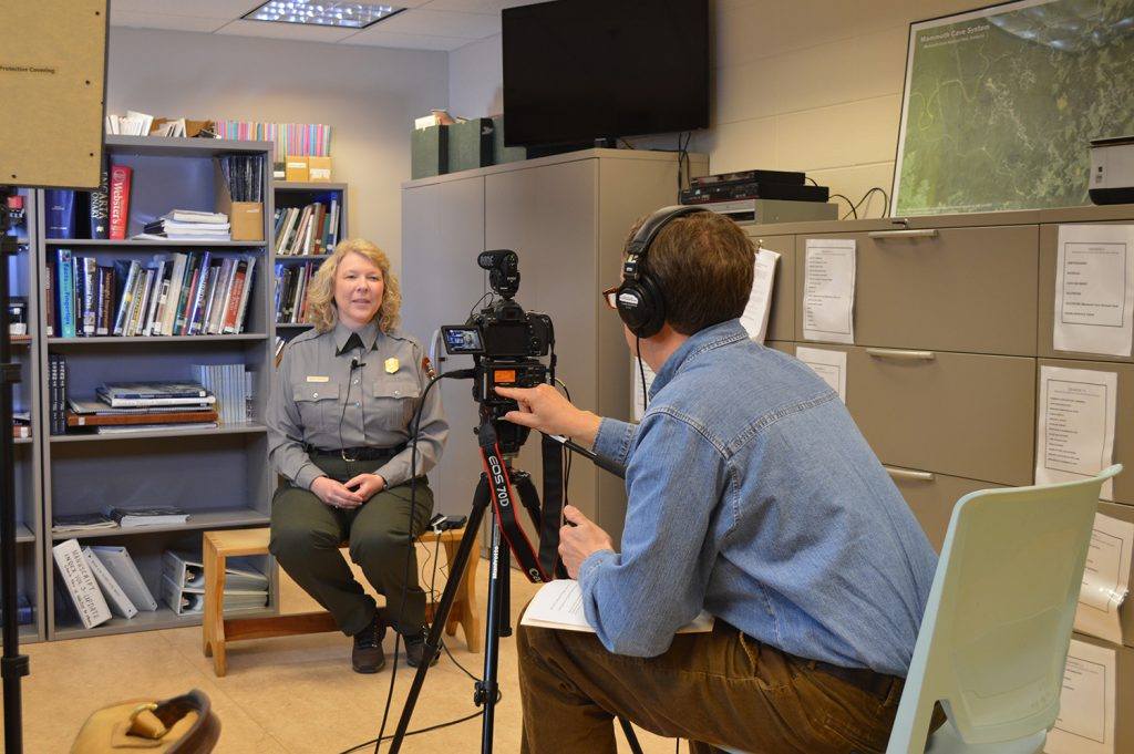 Woman in a park ranger's uniform interviewed by a man operating a video camera and wearing headphones.