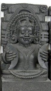 A sculpture of the upper torso of a god in black stone. He holds two crecent moons, one in each hand..