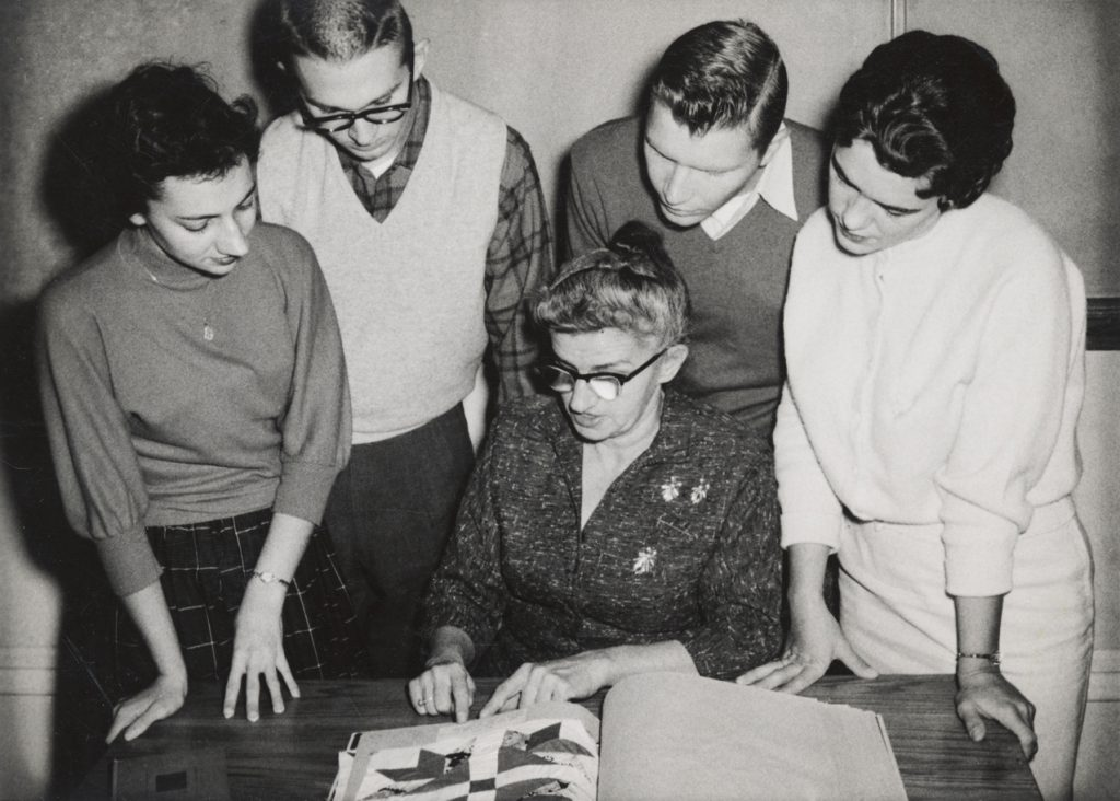 A woman sits, pointing at a caption which is pasted in a scrapbook underneath swatch of quilt. Two men and two women stand behind her, reading along with her.