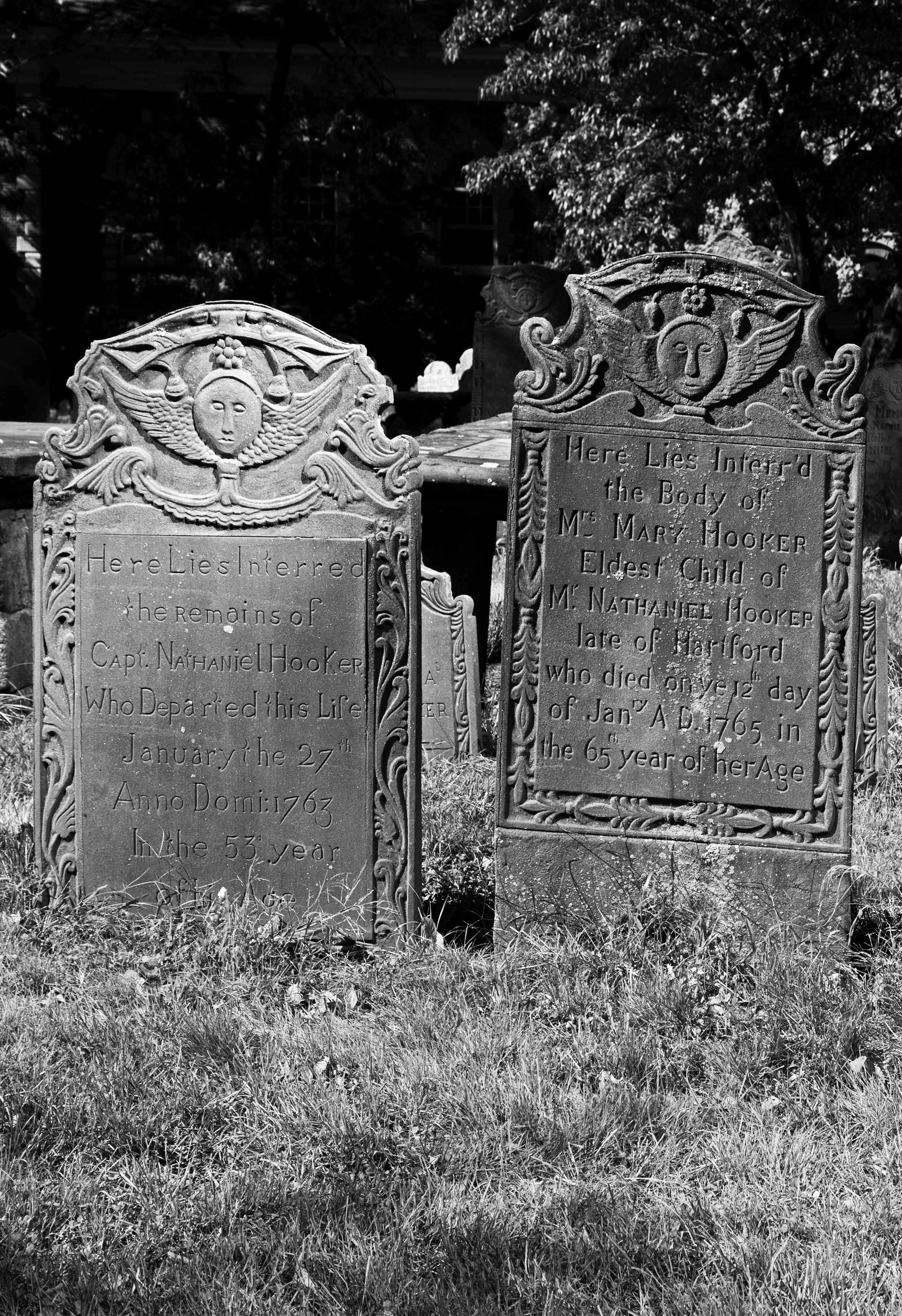 Two 18th century tombstones. Each has a stylized angel face and wings at the top and an inscription.