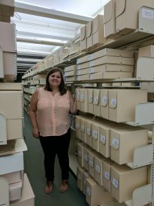 A photo of Kaitlin Dotosn standing next to archival boxes holding the collection of Connie Regan-Blake in the American Folklife Center.
