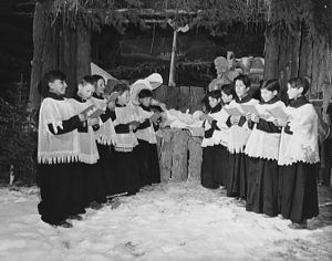 Choir boys sing outdoors in the snow in front of a Nativity display.
